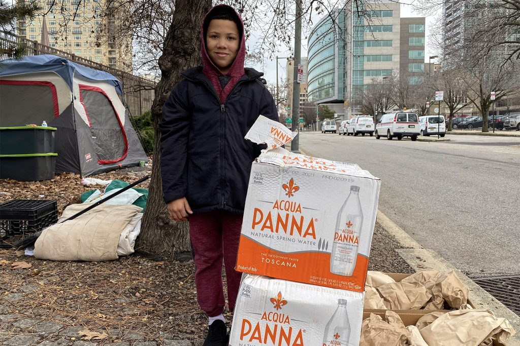 Xavier Bullock, 9, delivers water to people living at 18th and Vine