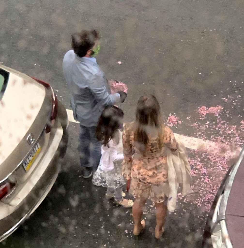 The surprise flower girl tossed petals from across the street