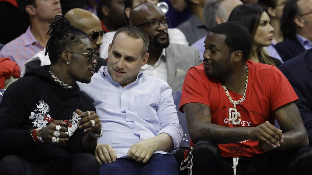 Sixers co-owner Michael Rubin, center, talks with rappers Lil Uzi Vert, left, and Meek Mill during the first half of Game 4 of an NBA basketball second-round playoff game in 2018