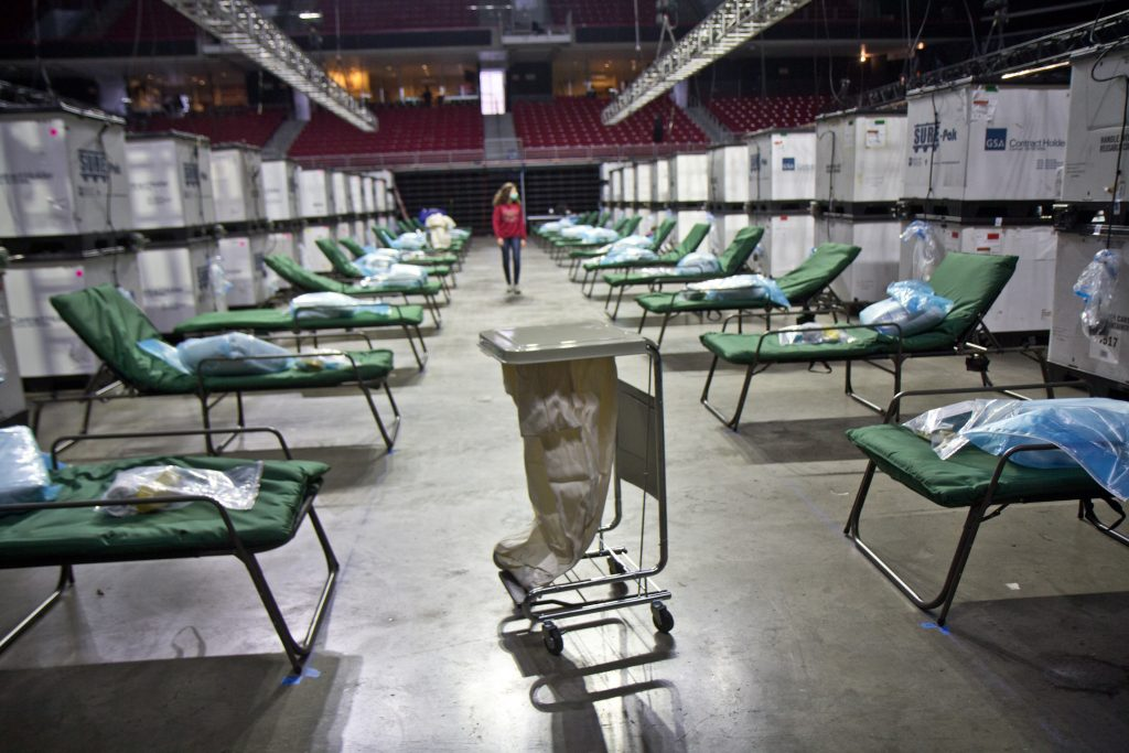 Temple University nursing students work to prepare 180 beds at the Liacouras Center, which is set to open Monday to accommodate an overflow of COVID-19 patients in Philadelphia. (Kimberly Paynter/WHYY)