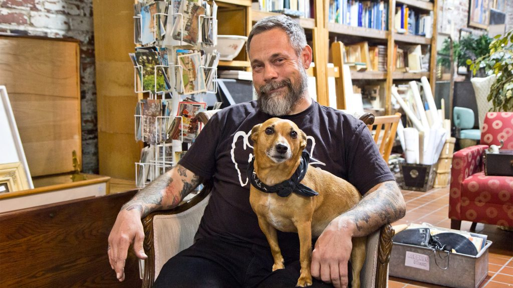 Mike 'Supermodel,' the owner of Jinxed stores, with his dog Ronnie