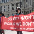 City employees staged a socially distant rally outside City Hall to protest planned layoffs