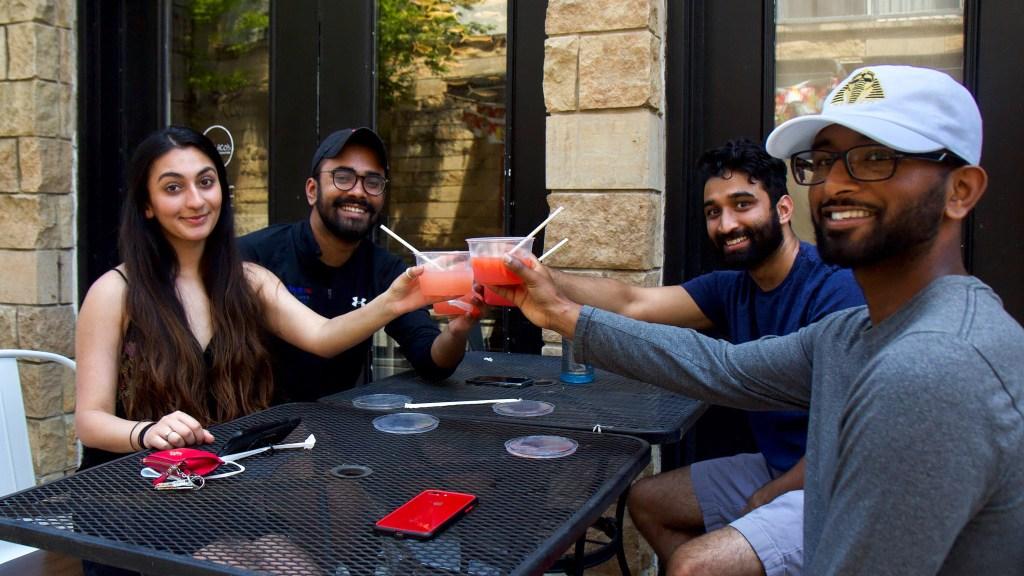 Rayyan Aziz (front left), Joel James (back left), Ravi Patel (back right) and Sean Shaji (front right) toast with margaritas at Set NoLibs