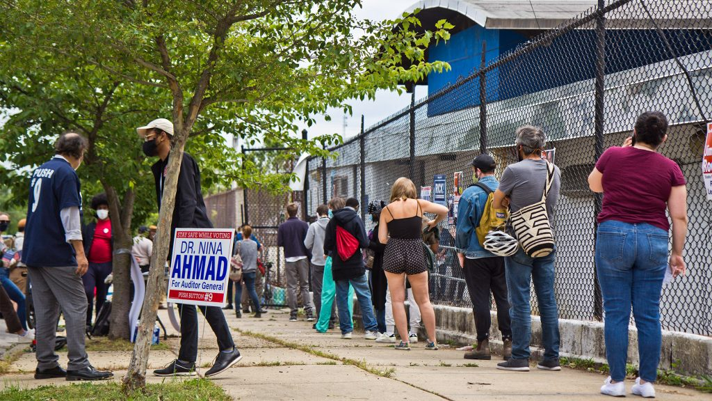 Voters wait in a socially distanced line outside their polling place in Philadelphia