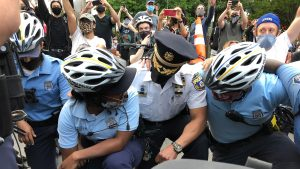 Officer Quishanna Lee, who has served on the force for three years, knelt with protesters Tuesday, and cried