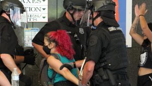 Police lead a protester away during a protest inside Philly's Municipal Services Building on June 23, 2020