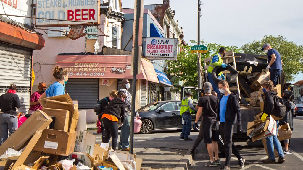 Clean-up volunteers and Clip workers in West Philadelphia work to sweep up glass and collect trash