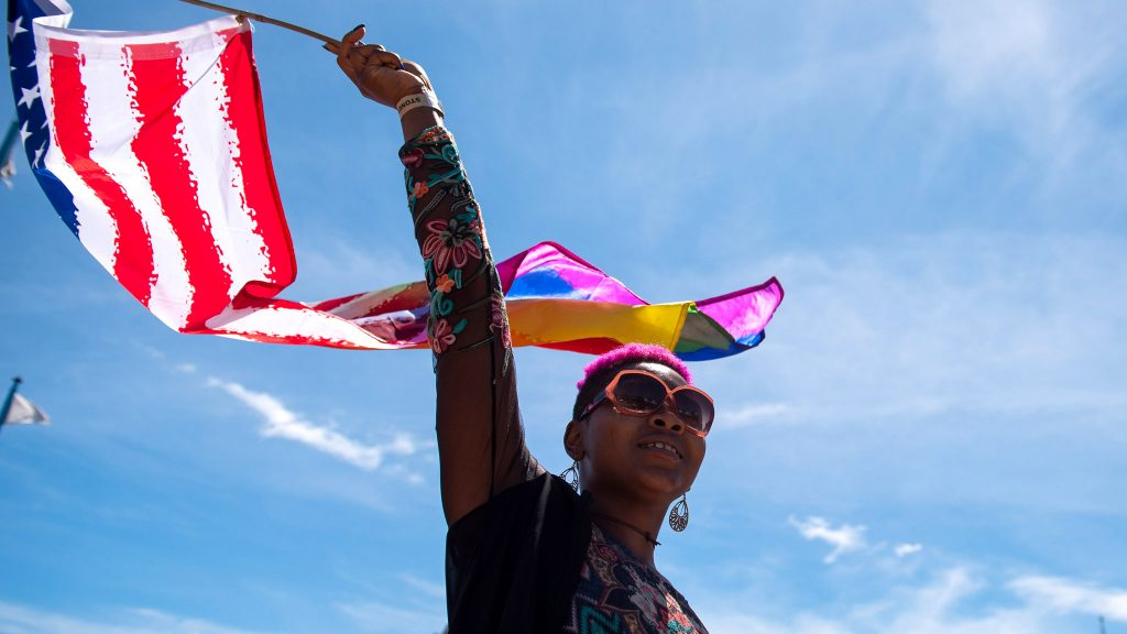 A participant in Philly's 2019 Pride Day Parade waves a rainbow-edged American flag
