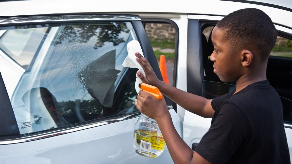 Jabre Dutton, 11, washes the windows of a client's car