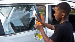 Jabre Dutton, 11, washes the windows of a client's car