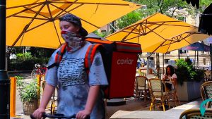 A food delivery courier passes an outdoor dining room in Philly's Rittenhouse neighborhood
