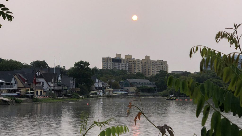 A haze of high-atmosphere smoke obscured the sun over Boathouse Row on Sept. 16