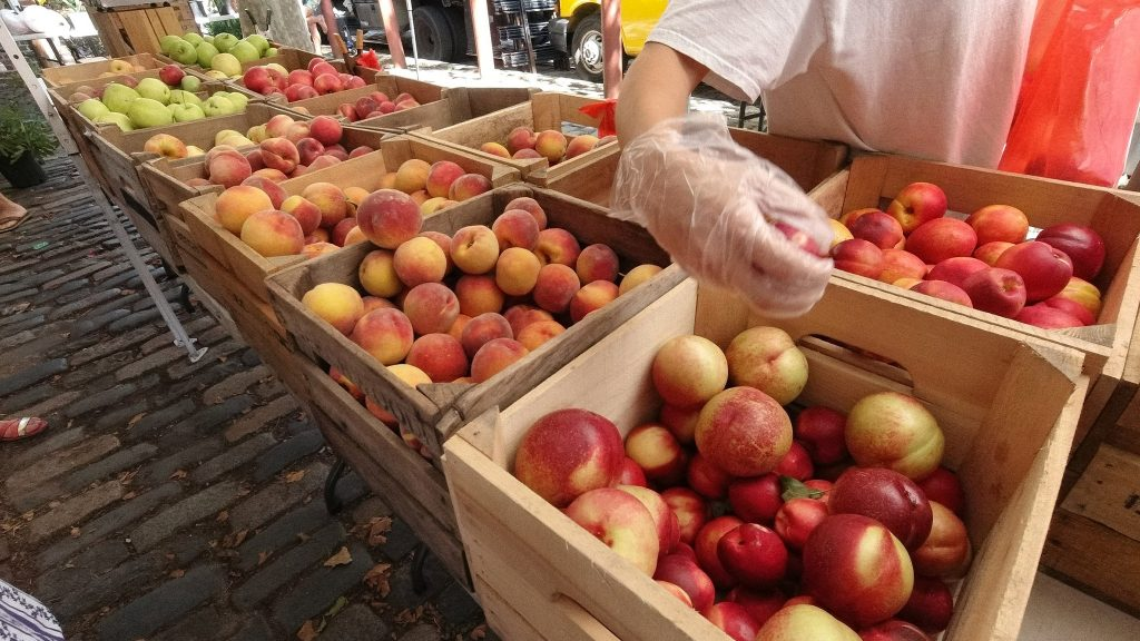 A representative at Beachwood Farms' Headhouse Market stand uses a glove to pick apples for a customer, before the rules were relaxed