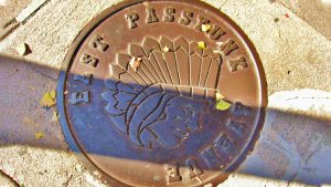 East Passyunk's current logo is seen on utility hole covers and flags along the avenue