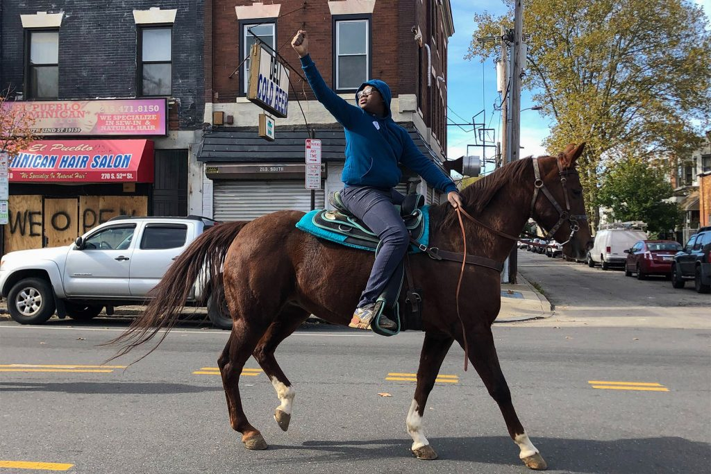 13-year-old Nahye Hyman raises a fist on his horse Sally during a GOTV ride down 52nd Street