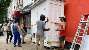Mina's World folks and friends installing the community fridge they maintain on 52nd Street