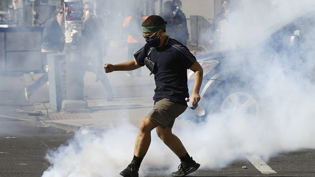 A protester kicks a tear gas canister fired by police during protests on Sunday, May 31, 2020, in Philadelphia