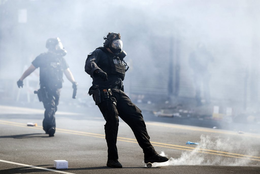 A police officer kicks a tear gas canister deployed to disperse a crowd during  protests on May 31, 2020