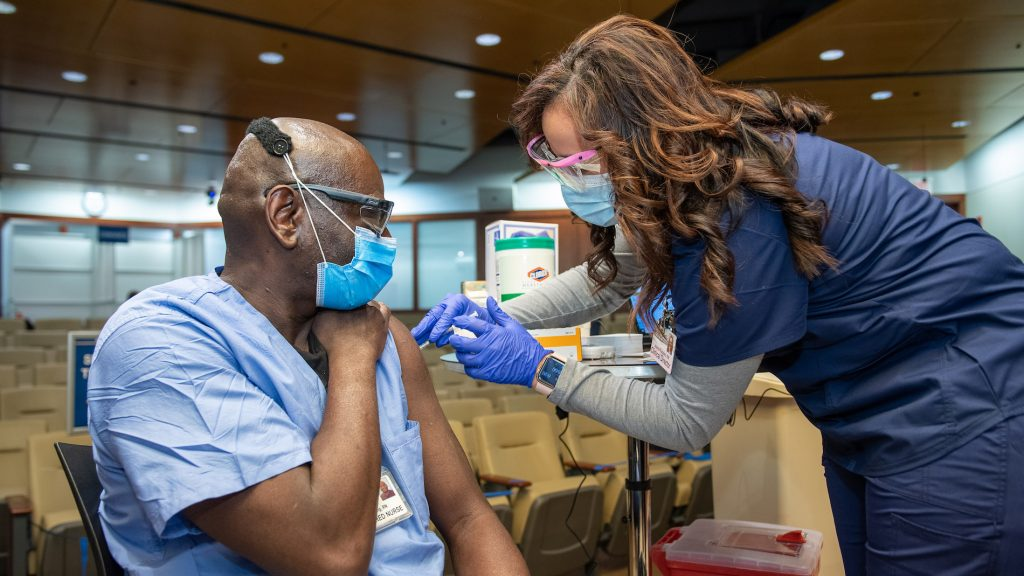 A health care worker receives a shot of the COVID-19 vaccine at Penn