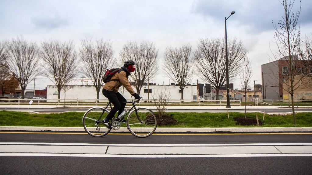 A cyclist uses the raised bike lane on North American Street