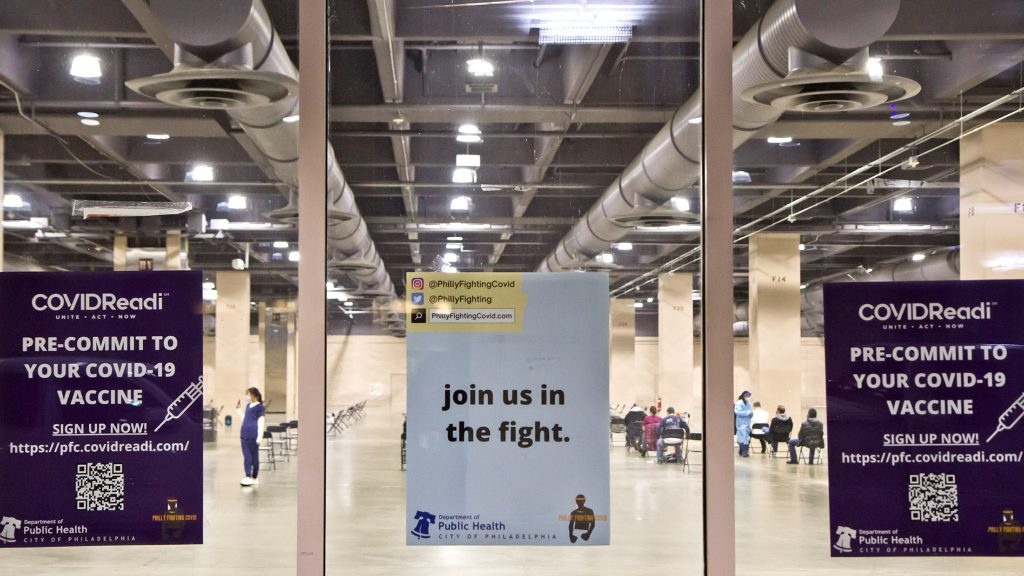 Signs on the window of the city's first mass vaccination at the Pa. Convention Center on its opening day, Jan. 8