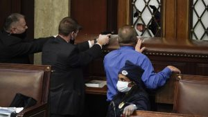 Police with guns drawn watch as insurrectionists try to break into the House Chamber at the U.S. Capitol on Wednesday
