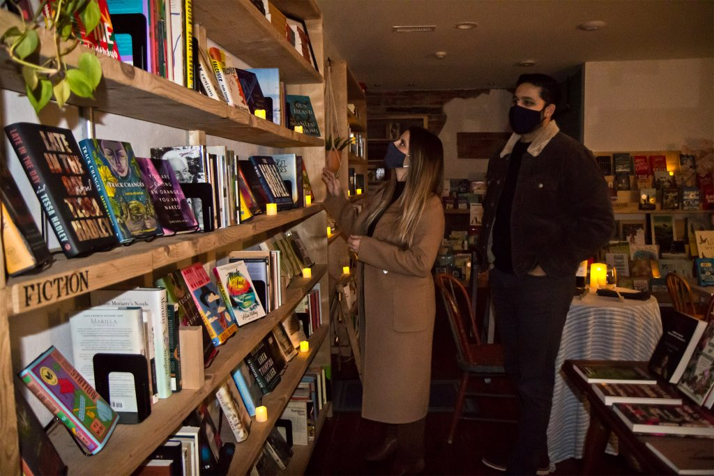 Tomaine and Sridharan browse the shelves before sitting down to their romantic dinner