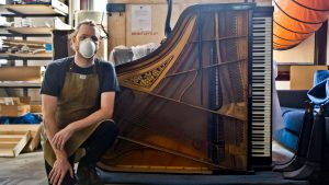 Restoration pro Tom Rudnitsky with the Frank-Brauer family piano, crafted a hundred years ago in Germany