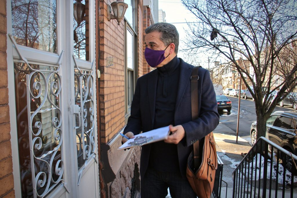 Carlos Vega carries a clipboard through his Point Breeze neighborhood, gathering petitions for his run for Philadelphia District Attorney. (Emma Lee/WHYY)