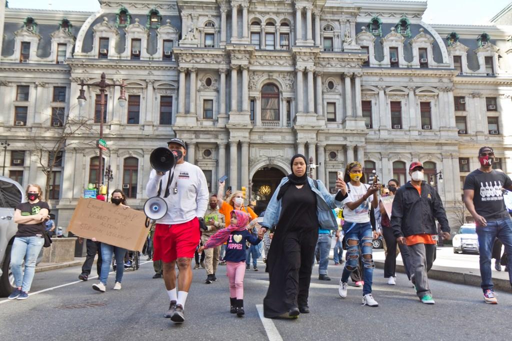 Philadelphians demanding more resources to combat gun violence speak on Broad Street in March 2021