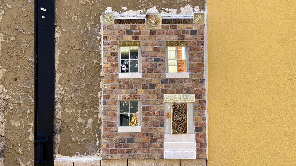 The miniature house has a real marble stoop and real brickwork in its facade