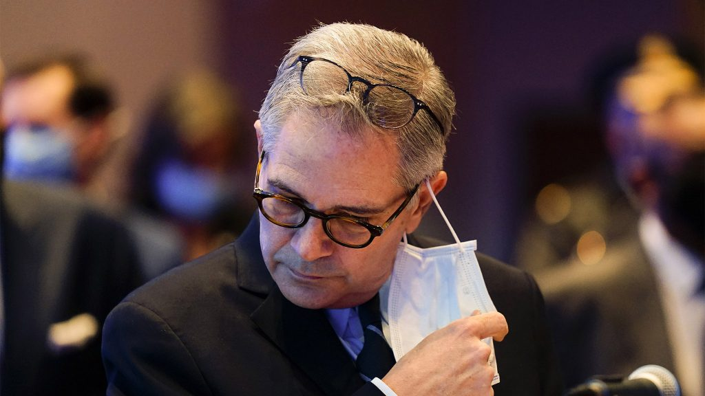 Philadelphia DA Larry Krasner removes his face mask to speak at a news conference in March 2021