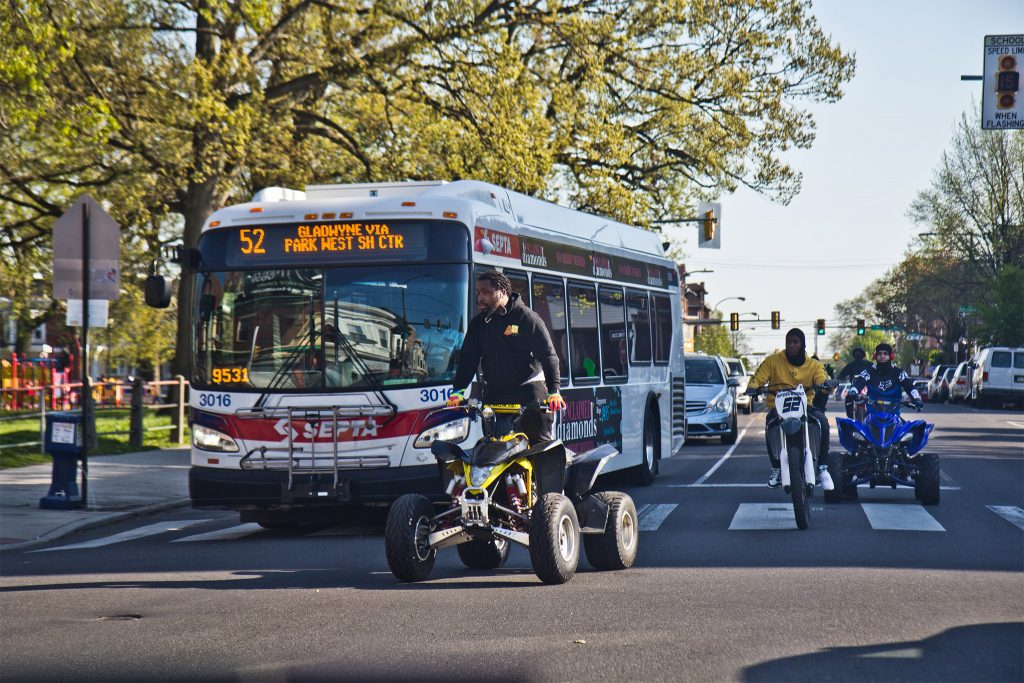 ATV and dirt bike riders zoom around a bus at 52nd and Pine streets in West Philadelphia