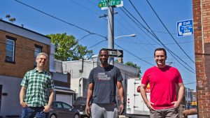 Organizers Ben Keys (left), Tyrique Glasgow (center), and Joshua Isserman (right), stand at the intersection of Tasker and Taney streets in South Philadelphia