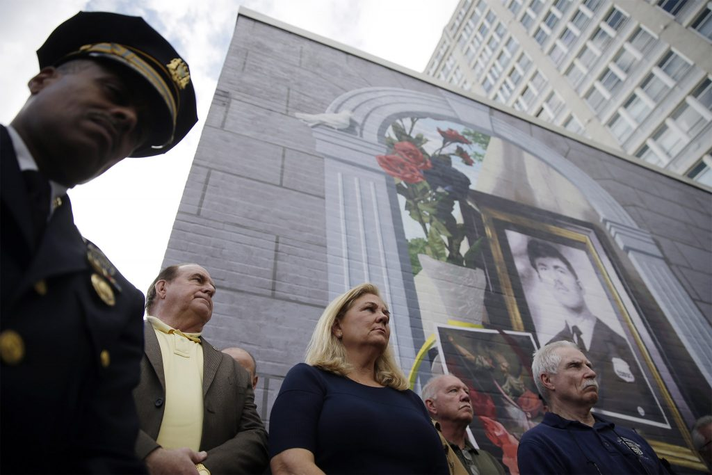 Maureen Faulkner (center), widow of Daniel Faulkner, stands in 2014 with his former colleagues and then-Deputy Police Commissioner Richard Ross (left), under a new mural of her husband