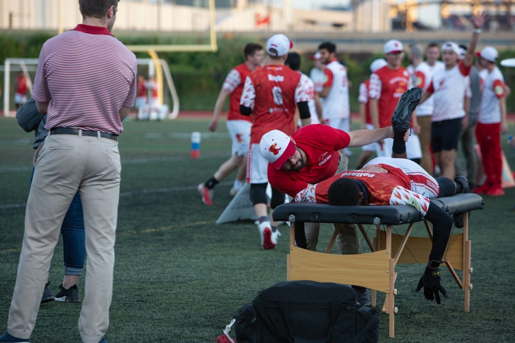 Head athletic trainer Josh McCune helps Phoenix player James Pollard stretch after Pollard fell during a play