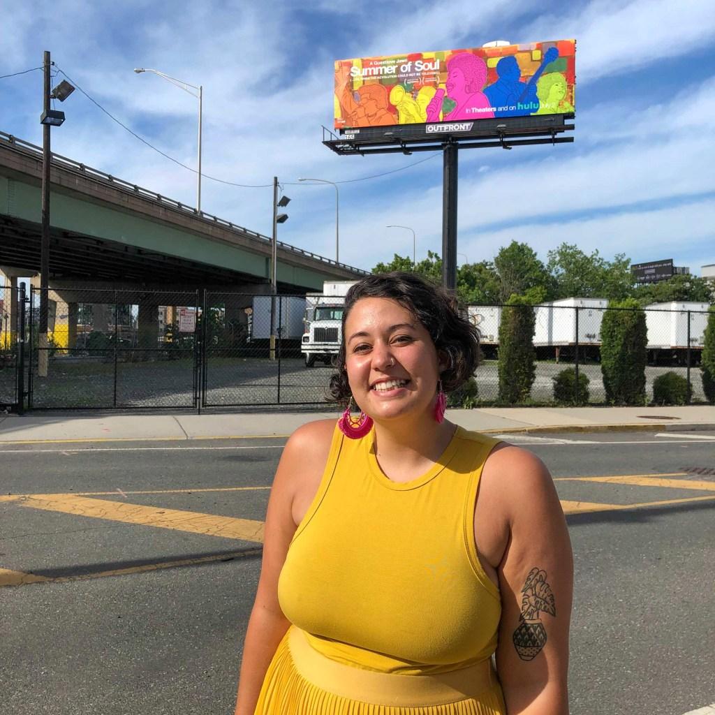 Artist Symone Salib in front of her 'Summer of Soul' billboard on I-95