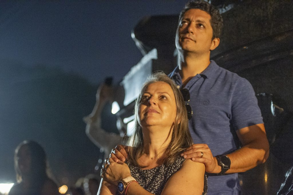 Beneath the statue of George Washington on Eakins Oval, a couple watches the fireworks display