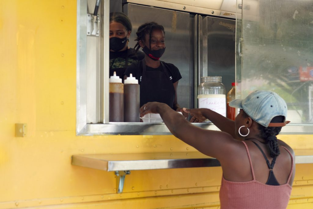 Customers place orders and pay at a window in the yellow food truck, which pulls a giant smoker