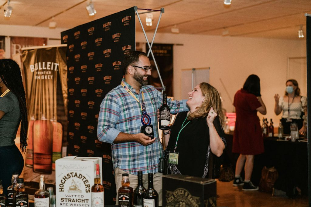 A rep from Cooper Spirits accepting an American Whiskey Convention award from Laura Fields