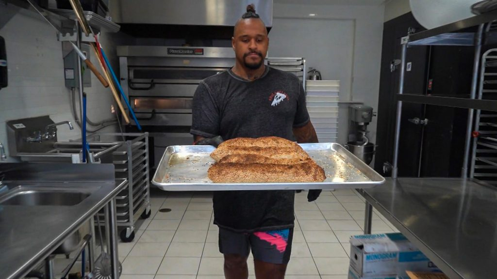 Chef David Lee carries loaves of lard bread at Pizza Jawn