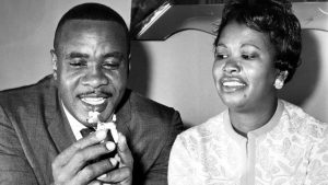 Sonny Liston holds a china dog from his collection as he sits with his wife Geraldine in their Philadelphia home in October 1962